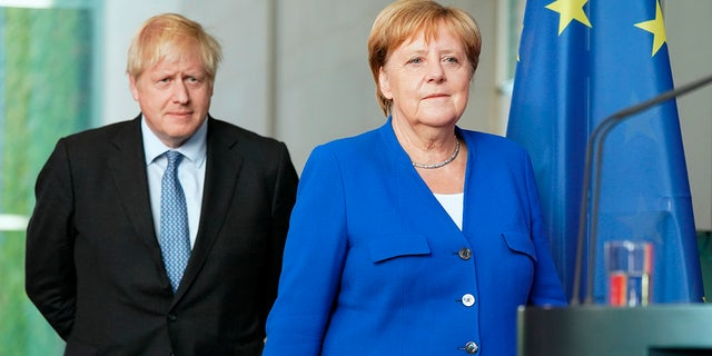 "Germany's Chancellor Angela Merkel and British Prime Minister Boris Johnson arrive for a joint press conference, in Berlin, Wednesday, Aug. 21, 2019. German Chancellor Angela Merkel says she plans to discuss with UK Prime Minister Boris Johnson how Britain's exit from the European Union can be ""as frictionless as possible."""