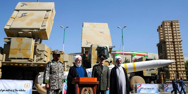 Iran's President Hassan Rouhani, second left, speaks during a ceremony to unveil the Iran-made Bavar-373, a long-range surface-to-air missile system at an undisclosed location in Iran, Thursday, Aug. 22, 2019.