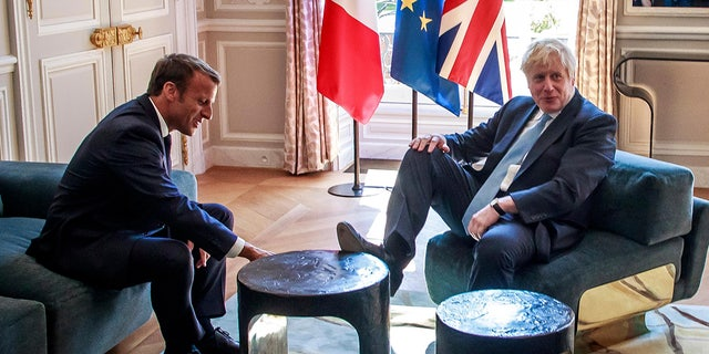 French President Emmanuel Macron, left, talks to Britain's Prime Minister Boris Johnson during their meeting at the Elysee Palace, Thursday, Aug. 22, 2019 in Paris.