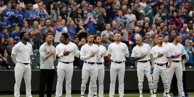 "Toronto Blue Jays players stand during the singing of the national anthem as they wear special MLB ""Players Weekend"" jerseys before a baseball game against the Seattle Mariners, Friday, Aug. 23, 2019, in Seattle. (Associated Press)"
