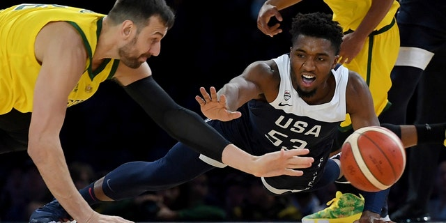 Australia's Andrew Bogut, left and United States Donovan Mitchell, right compete for the ball during their exhibition basketball game in Melbourne on Saturday. (AP Photo/Andy Brownbill)