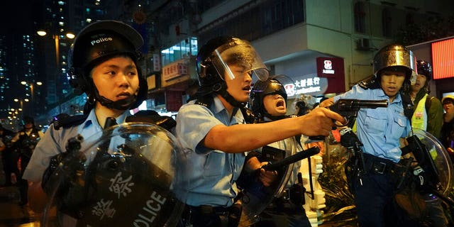 Policemen pull out their guns after a confrontation with demonstrators during a protest in Hong Kong on Sunday in the outlying Tsuen Wan district.