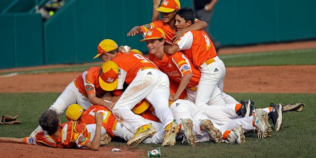 Louisiana's Stan Wiltz embracing Peyton Spadoni (6) as they jump on top of Jeffrey Curtis and Conner Perrot (9) celebrating the 8-0 win against Curacao in the Little League World Series championship game. (AP Photo/Tom E. Puskar)