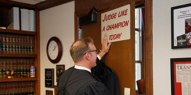 Judge Thad Balkman posing for a photo with the sign above his door before the court session to announce his decision in the oipiod lawsuit. (AP Photo/Sue Ogrocki, Pool)