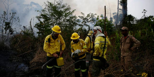 Firefighters rest briefly as they put out fires along the road to Jacunda National Forest, near the city of Porto Velho in the Vila Nova Samuel region which is part of Brazil's Amazon, Monday, Aug. 26, 2019.