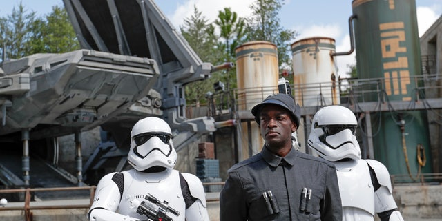 A First Order officer, center, and two storm troopers on patrol during a preview of the Star Wars-themed land, Galaxy's Edge in Hollywood Studios at Disney World, Tuesday, Aug. 27, 2019, in Lake Buena Vista, Fla. The attraction will open Thursday to park guests. (AP Photo/John Raoux)