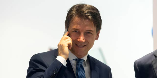 Italy's Prime Minister, Giuseppe Conte, talks at the phone inside a mobile phones shop in the center of Rome, Tuesday, Aug. 27, 2019.
