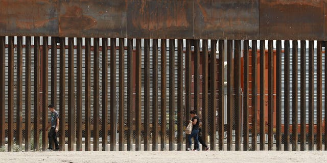 Three migrants who managed to evade the Mexican National Guard and cross the Rio Grande onto U.S. territory walked along a border wall set back from the geographical border, in El Paso, Texas, as seen from Ciudad Juarez, Mexico. (AP Photo/Christian Chavez, File)