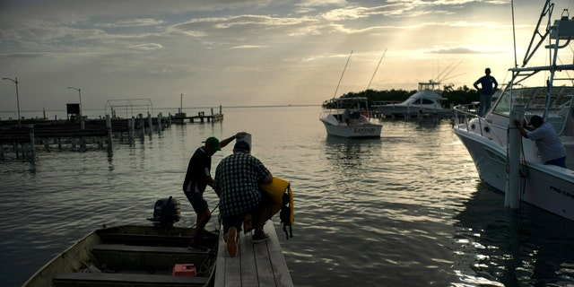 People arrive to a private harbor to move boats away for protection ahead of the arrival of Tropical Storm Dorian in Boqueron, Puerto Rico, Tuesday, Aug. 27, 2019. (AP Photo/Ramon Espinosa)