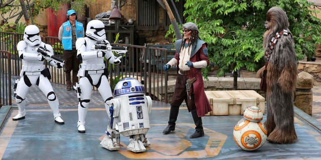 Chewbacca and Weequay pirate Hondo Ohnaka are caught by surprise as Stormtroopers interrupt the dedication ceremony looking for resistance fighters, at the entrance of the Star Wars: Galaxy's Edge attraction at Disney's Hollywood Studios in Lake Buena Vista, Fla., Wednesday, Aug. 28, 2019. The Star Wars-themed land at Disney World officially opens to guests on Thursday. (Joe Burbank/Orlando Sentinel via AP)