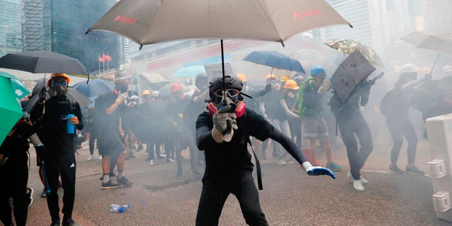 Protestors run for cover from tear gas shells in Hong Kong, Saturday, Aug. 31, 2019. Many of the protesters outside Hong Kong government headquarters have retreated as large contingents of police arrive on the streets in what looks like preparation for a clearing operation. Police were using tear gas Saturday to drive back remaining protesters.