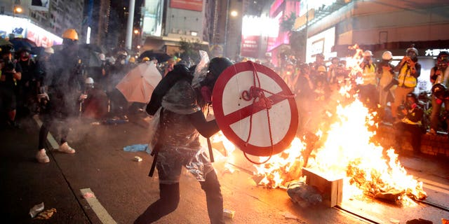 A protestor uses a shield to cover himself as he faces policemen in Hong Kong, Saturday, Aug. 31, 2019. Protesters and police are standing off in Hong Kong on a street that runs through the bustling Causeway Bay shopping district. (AP Photo/Jae C. Hong)