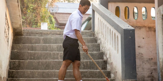 Adun Samon doing his morning chores at the church hostel before going to school.