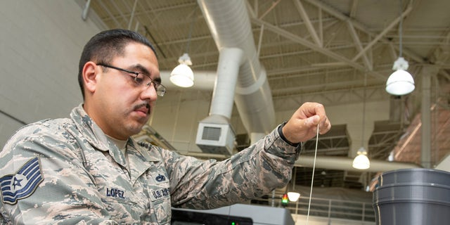 U.S. Air Force Tech. Sgt. Rogelio Lopez, 60th Maintenance Squadron assistant aircraft metals technology section chief, loads Ultem 9085 material into a canister for use in the Stratasys F900 three-dimensional printer Aug. 15, 2019, Travis Air Force Base, California.