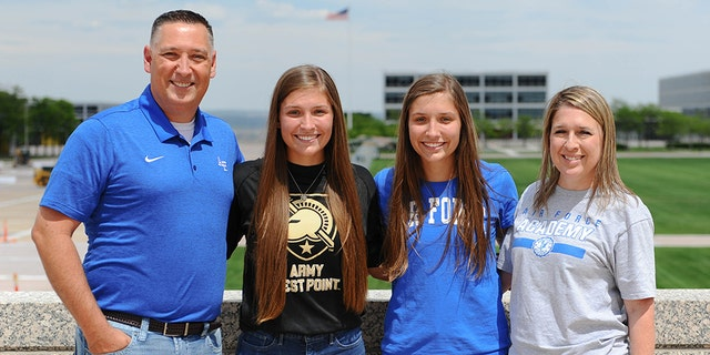 Aubrie and EmmaKuhrt (center), twin sisters from Texas who split to attend separate U.S. military academies, with their parents, Michael (left) and Shannon (right). (U.S. Air Force Academy Public Affairs)