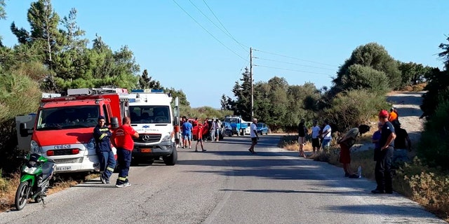 Authorities and residents gather near the location where police said the body of Cyprus-based astrophysicist Natalie Christopher, 35, was found in a 65-foot deep ravine, in Faros village on the Greek island of Ikaria, Wednesday, Aug. 7, 2019.