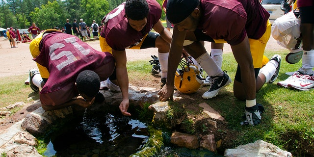 FILE - In this Aug. 15, 2012, file photo, Arizona State wide receivers Rashad Ross, left, JJ Holliday, center, and Alonzo Agwuenu drink water from a spring after NCAA college football practice at Camp Tontozona in Kohls Ranch, Ariz.  (Michael Chow/The Arizona Republic via AP, File)