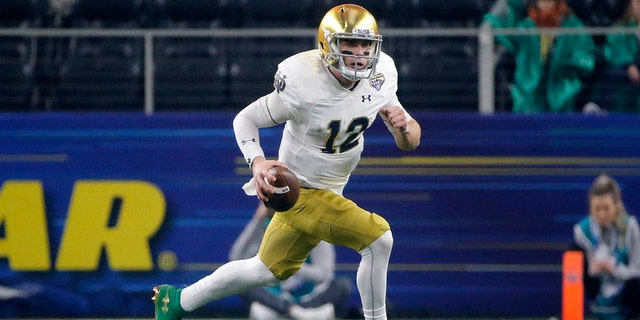 FILE - In this Dec. 29, 2018, file photo, Notre Dame quarterback Ian Book (12) runs the ball against Clemson during the NCAA Cotton Bowl semifinal playoff football game, in Arlington, Texas. Upon his return to campus last winter, Book immediately worked on his leadership skills and also making the difficult and tight downfield passes. Book was rewarded when he was named one of the team's seven captains. (AP Photo/Michael Ainsworth, File)