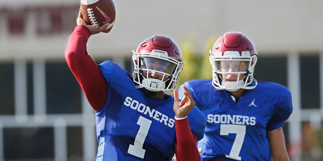 FILE - In this Monday, Aug. 5, 2019, file photo, Oklahoma quarterback Jalen Hurts (1) throws as quarterback Spencer Rattler watches during the NCAA college football team's practice in Norman, Okla. Oklahoma coach Lincoln Riley has chosen Hurts as his starting quarterback for the Sept. 1 season opener against Houston over Rattler and Tanner Mordecai. (AP Photo/Sue Ogrocki, File)