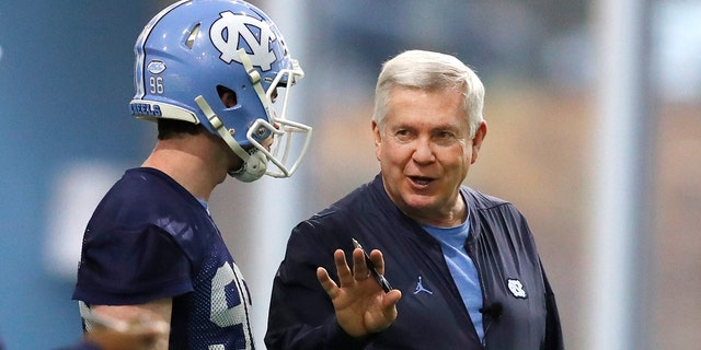 FILE - In this March 3, 2019, file photo, North Carolina head coach Mack Brown talks with Cooper Graham (96) during UNC's first spring football practice, in Chapel Hill, N.C. Brown is savoring his return to coaching in a second stint with the Tar Heels. (Ethan Hyman/The News & Observer via AP, File)