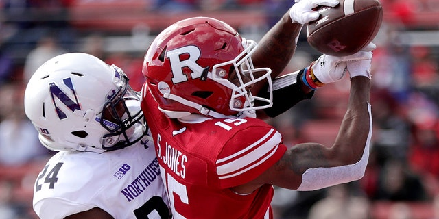 """FILE - In this Oct. 20, 2018 file photo, Northwestern cornerback Montre Hartage, left, deflects a pass as Rutgers wide receiver Shameen Jones tries to make the catch in the end zone during the second half of an NCAA college football game in Piscataway, N.J. New Jersey's flagship university has asked a high school in northern Louisiana to change its logo because it's identical to the block """"R'' that Rutgers has trademarked. (AP Photo/Julio Cortez, File)"""