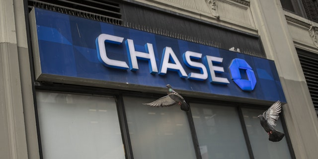 "Signage is displayed outside a JPMorgan Chase & Co. bank branch in New York. The bank has decided to ""forgive"" all outstanding balances for Canadians who use their two credit cards following an exit from the market. Victor J. Blue/Bloomberg via Getty Images"