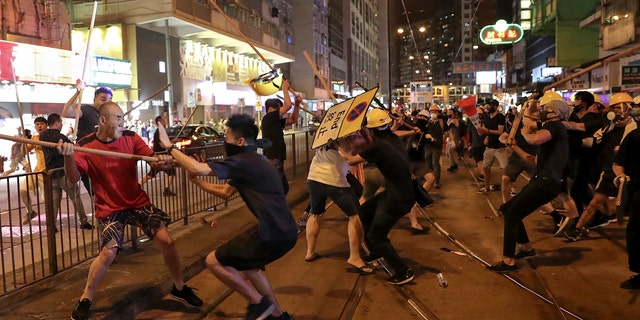 In this Monday, Aug. 5, 2019, photo, protesters wearing black shirt, right, fight with a group of men wielding wooden poles on a street during the anti-extradition bill protest at a neighborhood in Hong Kong.