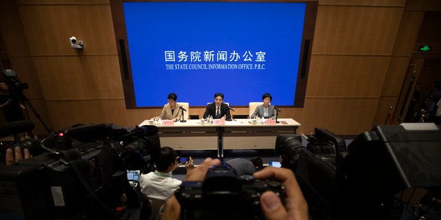 Yang Guang, center, spokesman for the Chinese Cabinet's Hong Kong and Macao Affairs Office, speaks during a press conference in Beijing, Tuesday, Aug. 6, 2019.
