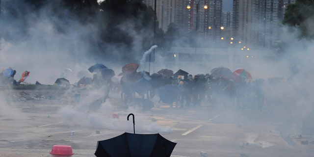 An umbrella is abandoned as protesters pull back from tear gas on Monday, Aug. 5, 2019.