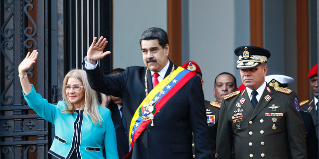 Venezuela's President Nicolas Maduro, center, and first lady Cilia Flores, wave to supporters as they leave the National Pantheon after attending a ceremony to commemorate an 1800's independence battle, in Caracas, Venezuela, Wednesday, Aug. 7, 2019.