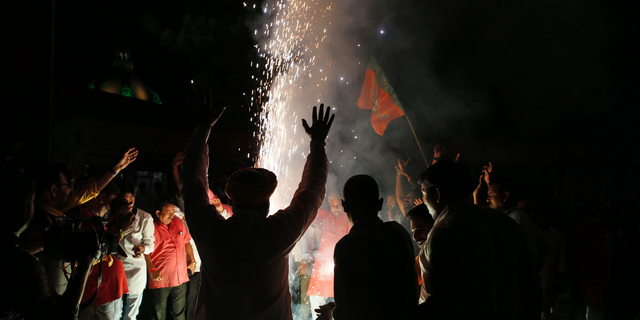 Supporters of India's ruling Bharatiya Janata Party (BJP) light firecrackers and celebrate the government revoking Kashmir's special status, in Lucknow, India, Tuesday, Aug. 6, 2019. Indian lawmakers passed a bill Tuesday that strips the statehood from the Indian-administered portion of Muslim-majority Kashmir amid an indefinite security lockdown in the disputed Himalayan territory, actions that neighboring Pakistan warned could lead to war.