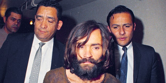 Charles Manson is escorted to his prosecution on conspiracy-murder charges in tie with a Sharon Tate murder box in Los Angeles. (AP Photo/File)