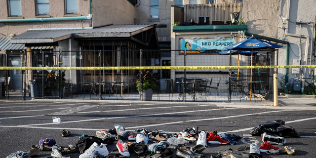 Shoes are piled outside the scene of a mass shooting including Ned Peppers bar, Sunday, Aug. 4, 2019, in Dayton, Ohio.