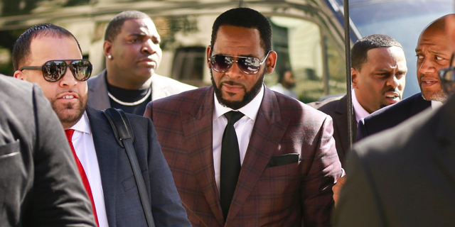 R. Kelly, center, arrives at the Leighton Criminal Court building for an arraignment on sex-related felonies in Chicago on June 26, 2019. (AP Photo/Amr Alfiky, File)