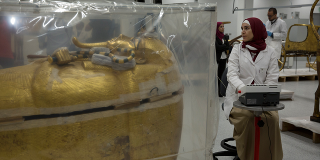 The gold-covered sarcophagus of King Tutankhamun is encased in a tent for restoration procedures at the conservation center of the Grand Egyptian Museum in Giza, near Cairo, Egypt, Sunday, Aug. 4, 2019. (Associated Press)