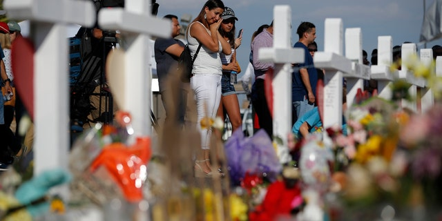 People visit a makeshift memorial, Monday, Aug. 5, 2019, at the site of a mass shooting at a shopping complex, in El Paso, Texas.