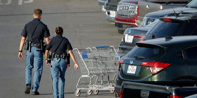 Police officers walk by shopping carts at the scene of a mass shooting at a shopping complex Sunday, Aug. 4, 2019, in El Paso, Texas.