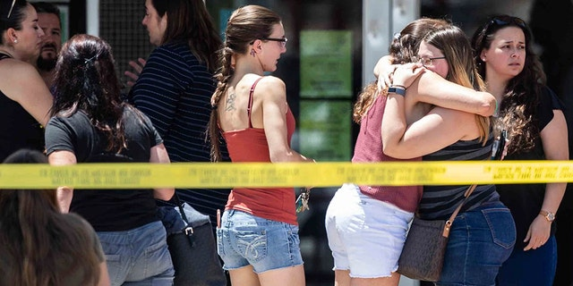 Family members hug to each other outside the family reunification center at MacArthur Elementary-Intermediate School in El Paso, Texas on Sunday, Aug. 4, 2019.