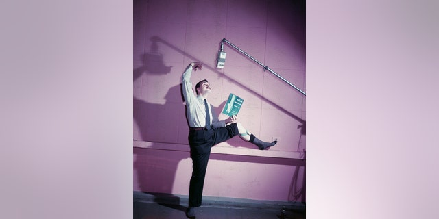 American actor Ernie Kovacs (1919 - 1962) posing in a ballet stance while holding a ballet book inside a WABC radio recording studio, 1950s.