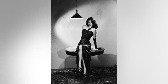 "Ava Gardner poses in a sleek black satin dress in a scene from Robert Siodmak's film noir, ""The Killers,"" in 1964. (Photo by Ray Jones/John Kobal Foundation/Getty Images)"