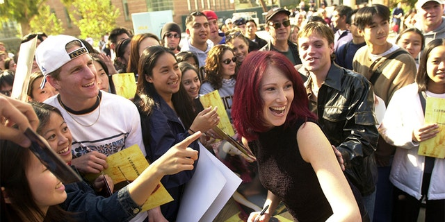Pop music singer Tiffany laughs with fans while signing autographs November 16, 2000, after a free concert at the University of California Los Angeles in Los Angeles. (Photo by David McNew/Newsmakers)