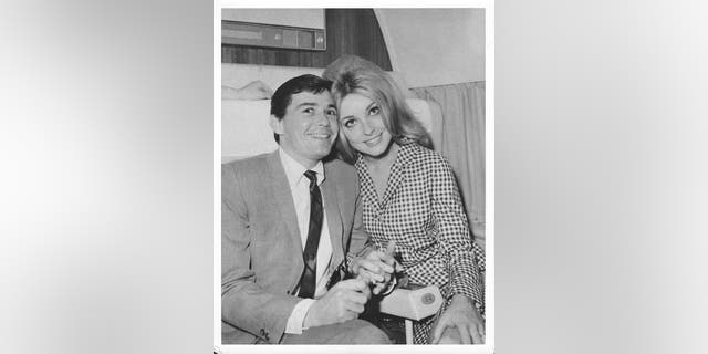Actress Sharon Tate and hairdresser Jay Sebring pose for a portrait on a plane circa 1966. (Photo by Michael Ochs Archives/Getty Images)