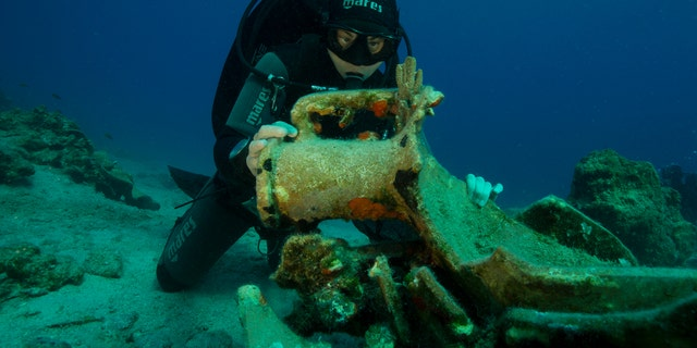 A diver inspects an amphora, or ancient jar, on the seabed.