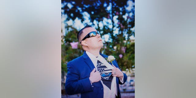"""Peter Herrera often wore the Blue Lives Matter shirt, even under suits. His mother Esther says that in this photo, """"Peter looks like he's looking up at the Lord."""""""