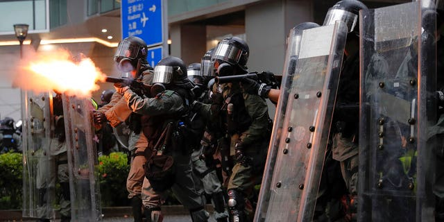 Riot police fires tear gas at protesters during a protest in Hong Kong, Sunday, Aug. 25, 2019. Police were skirmishing with protesters in Hong Kong for a second straight day on Sunday following a pro-democracy march in an outlying district. (AP Photo/Kin Cheung)