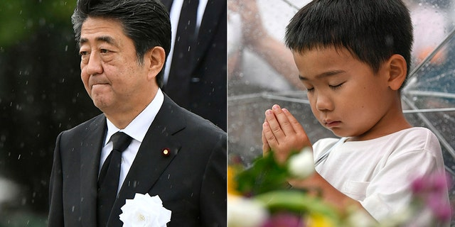 Japanese Prime Minister Shinzo Abe (left) leaves after his speech during a ceremony to mark the 74th anniversary of the atomic bombing at the Hiroshima Peace Memorial Park in Hiroshima, western Japan Tuesday, Aug. 6, 2019. A boy prays (right) for the atomic bomb victims in front of the cenotaph at the Hiroshima Peace Memorial Park in Hiroshima.