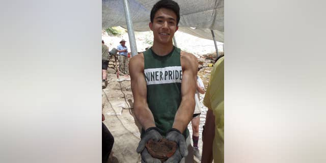 UNC Charlotte student Miles Shen holding a lamp dating from the Iron Age.