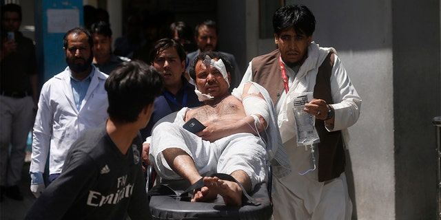 A wounded man is carried to an ambulance after an explosion in Kabul, Afghanistan. A suicide car bomber targeted the police headquarters in a minority Shiite neighborhood in western Kabul on Wednesday, setting off a huge explosion that wounded dozens of people, Afghan officials said.