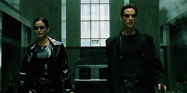 Kari-Anne Moss as Trinity and Keanu Reeves as Neo.