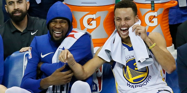 FILE - In this Nov. 22, 2017, file photo, Golden State Warriors forward Kevin Durant, left, and guard Stephen Curry, right, laugh on the bench during the third quarter of the team's NBA basketball against the Oklahoma City Thunder in Oklahoma City. (AP Photo/Sue Ogrocki, File)